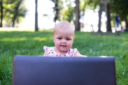 Baby girl sitting on the green grass with laptop Stock Photo