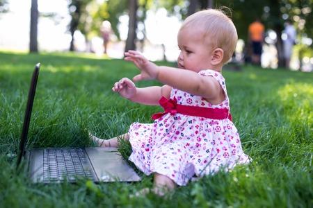 prodigy: Baby girl sitting on the green grass with laptop Zdjęcie Seryjne