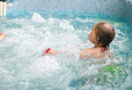 Happy little girl learning to swim with pool noodle. Standard-Bild - 98599541