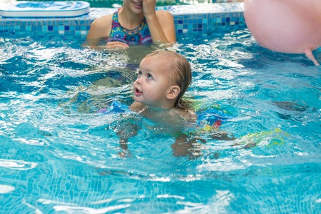 Mother with her lovely child in swimming-pool. Standard-Bild - 98599538