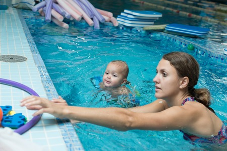 Mother with her lovely child in swimming-pool. Standard-Bild - 98599540
