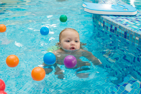 Happy little girl learning to swim with pool noodle. Standard-Bild - 96555070