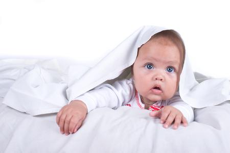 Glückliches Mädchen , das im Bett unter einer weißen Decke oder Bettdecke versteckt . Mädchen am Bett . Kind im Bett . Isoliert auf weißem Hintergrund Standard-Bild - 99230084