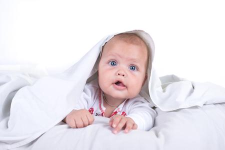 Glückliches Mädchen , das im Bett unter einer weißen Decke oder Bettdecke versteckt . Mädchen am Bett . Kind im Bett . Isoliert auf weißem Hintergrund Standard-Bild - 99230085
