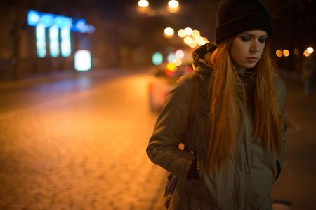 Young beautiful girl catches a taxi in the city street at night Standard-Bild