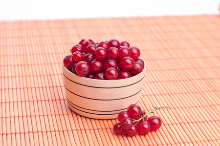 wet red currant on brown wooden table