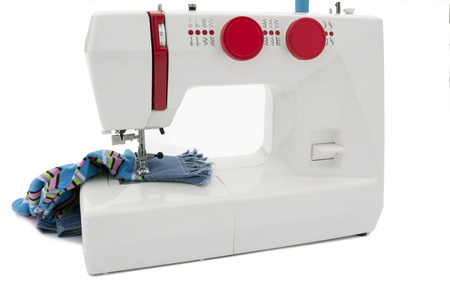 furnish: The electric sewing-machine with red furnish and a multi-coloured fabric on the isolated white background