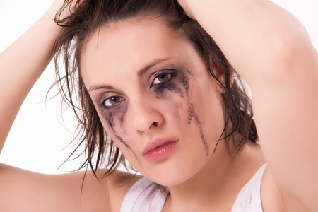 crying young woman with flowed mascara on white photo