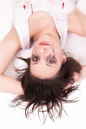 crying young woman lying on the floor on white photo