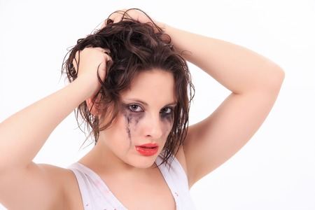 traumatised: crying young woman with flowed mascara isolated on white