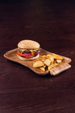 Close up Burger with beef, cheese and vegetables, garnished with potato wedges fried