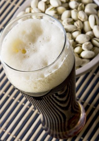 Beer with salty pistachio  close up photo
