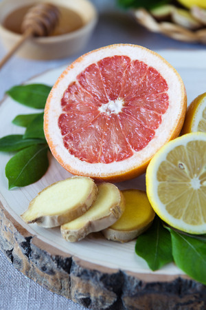grippe: Close up of a grapefruit, lemons and ginger on a wooden stand with a plate of honey