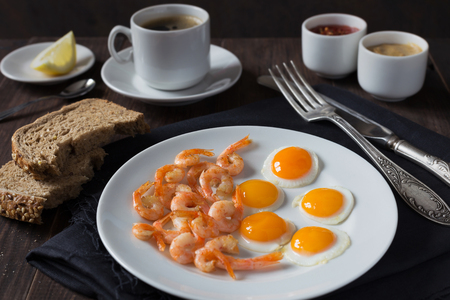 wholegrain mustard: A horizontal photo of a plate of fried quail eggs with shrimps
