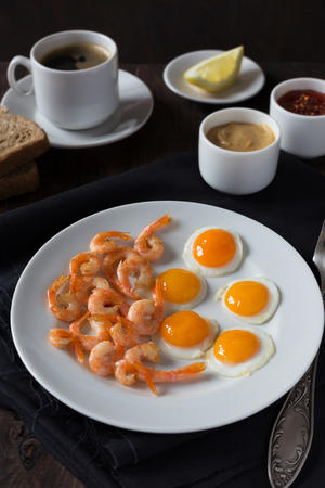wholegrain mustard: A vertical photo of Fried quail eggs and shrimps on a white plate