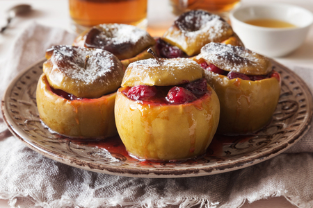 Horizontal photo of baked apples with cranberry and sugar powder Stock Photo