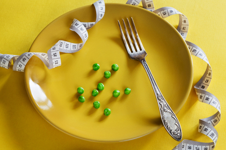 Horizontal photo of yellow plate with centimeter, peas and fork