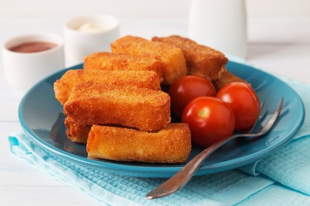 Horizontal photo of fried cheese sticks with tomatoes, a fork and sauces