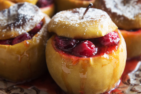 Horizontal photo of baked apples with cranberries and sugar powder
