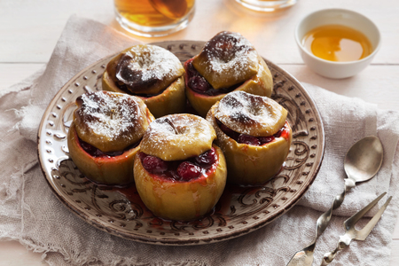 Horizontal photo of baked apples with cranberries and sugar powder on a plate Standard-Bild