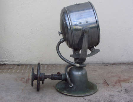 Antique search light used on boats weathered and rusting. Stock Photo