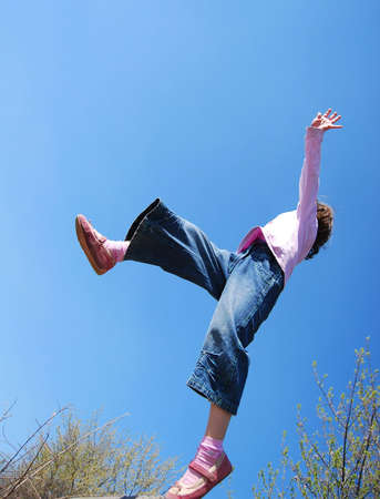 flying girl pink shoes and lilac pullover against blue sky background Stock Photo - 4778226