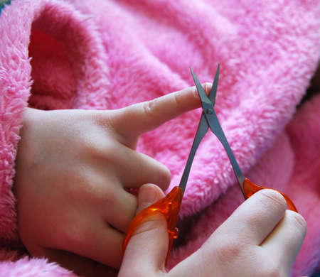 girl in pink garment cutting her nails with cosmetic scissors  photo