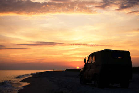 people on the beach at sunset time, parked car Stock Photo - 11790335