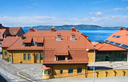 int: Yellow houses with tile roofs in Bergen, Norway, fjords and city int yhe horizon