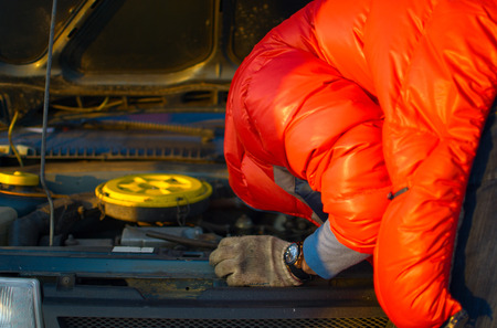 unprofessional: Driver checking car engine under the open hood, troubleshooter in red jacket