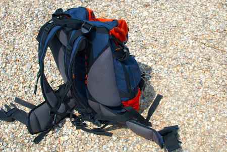 sports shell: Hiking backpack with tourist equipment for travelers, tourists backpack for low budget trips. Sea shore