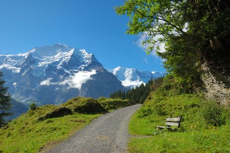 Bench beside a hiking trail with the snowcapped peaks of the Swiss Alps in the background. Stock Photo