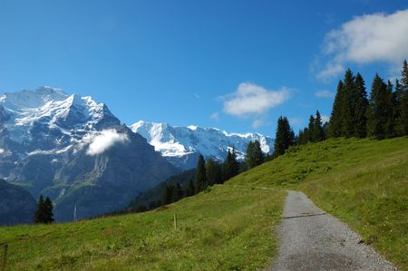 Hiking trail with the snowcapped peaks of the Swiss Alps in the background. Stock Photo