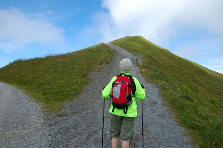 Middle-aged woman hiker with backpack facing a long trail up a mountain path.