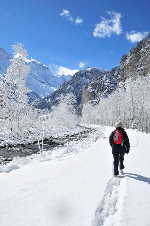 Lone hiker on river trail in snowcovered alpine valley.
