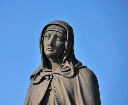 Statue of Mary on the Charles Bridge in Prague, Czech Republic against a blue sky.