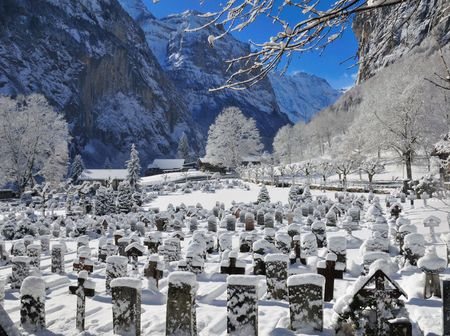 Snowcvered tombstones and valley vista in Swiss Alpine village Stock Photo