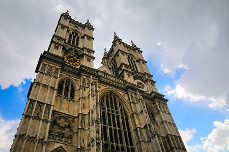 Towers of Westminster Abbey against a  blue sky with clouds.