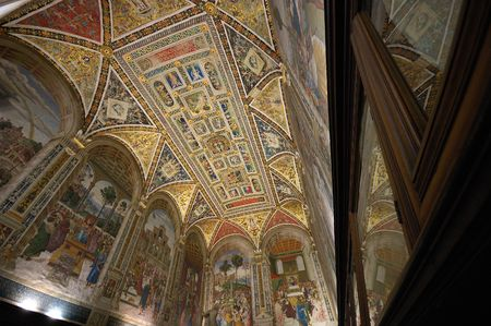 Interior of the Piccolomini library in the Siena Duomo cathedral showing the beautiful painted ceiling and frescoed walls. Stock Photo