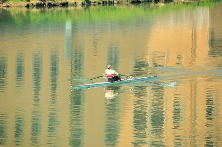sculling: Man rowing a single seat racing shell on the Arno river in Florence with the reflection of ancient building in the water.