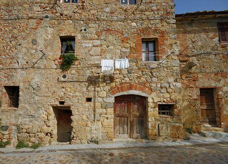 Oud stenen huis op een steen straat in de oude ommuurde stad Monteriggioni, Toscane, Italië Stockfoto