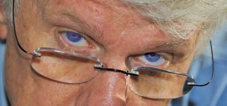 rimless: Serious look over rimless glasses. Stock Photo