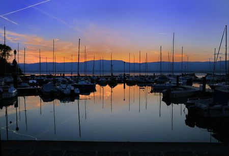 Summer sunset on a lake Geneva marina full of sailboats.