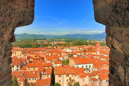 View of the red roofs of Lucca and distant countryside from the Guinigi tower.