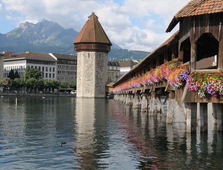 Famous Chapel Bridge and Mount Pilatus in Lucerne, Switzeland on a clear summer day.