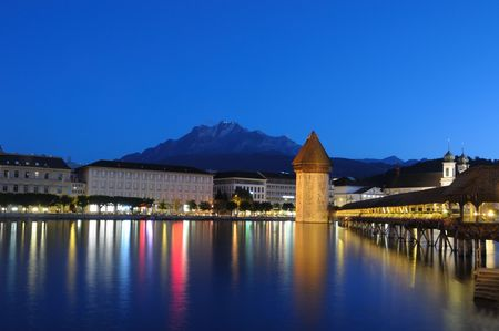 Famous Chapel Bridge and Mount Pilatus in Lucerne, Switzeland on a clear summer night.