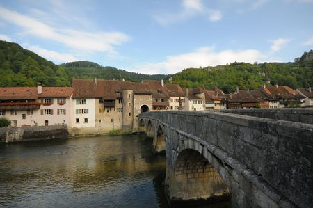 walled: Medieval bridge leading into the old walled city of St. Ursanne, Switzerland.  Stock Photo