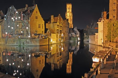 Night time scene of center town buildings and belltower reflected in canal in Brugge, Belgium