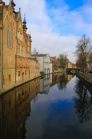 Brugge canal in winter with blue sky and clouds reflected with the old buildings in the water.