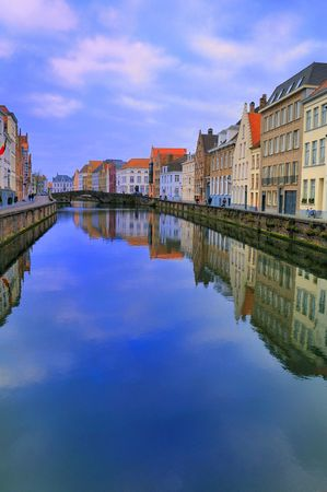 Brugge canal in winter with blue sky and clouds reflected with the residences in the water.